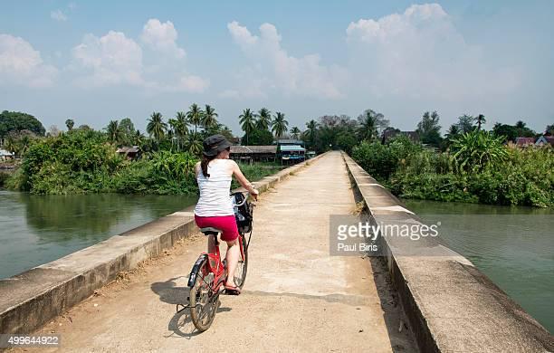 Rear view of female tourist cycling on Mekong riverbank, Don Det, Laos
