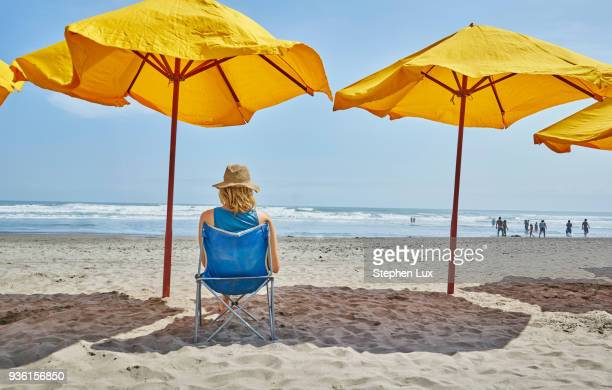 rear view of female tourist sitting under beach umbrella, camana, arequipa, peru - parasol stock pictures, royalty-free photos & images