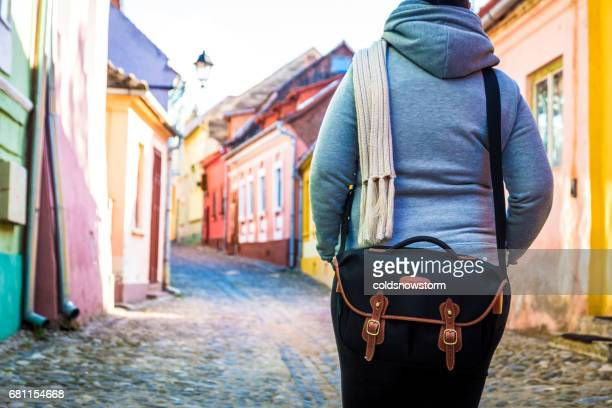 Rear view of female traveler wearing black shoulder bag with colourful houses blurred in the background