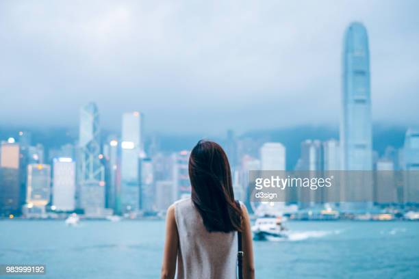 rear view of female traveller enjoys the view at victoria harbour and hong kong city skyline at dusk - wealth stock pictures, royalty-free photos & images