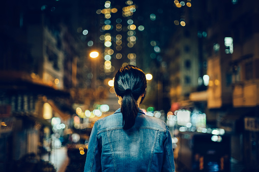 Rear view of female traveller exploring city streets and enjoying night scene of Hong Kong - gettyimageskorea