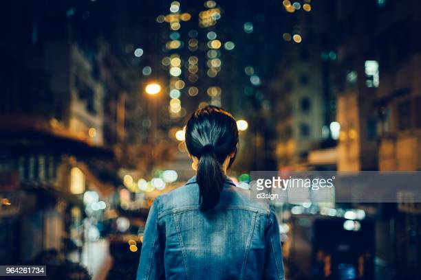 rear view of female traveller exploring city streets and enjoying night scene of hong kong - curiosity stock photos and pictures