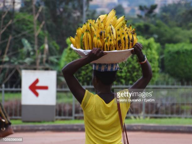 rear view of female vendor selling bananas on street - uganda stock pictures, royalty-free photos & images