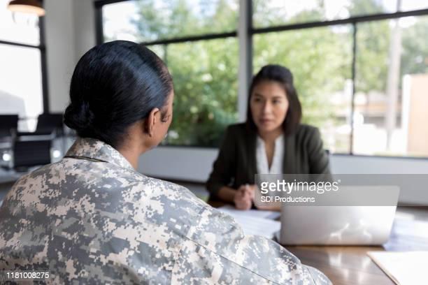 vue arrière du vétéran féminin parlant avec le conseiller - armée photos et images de collection