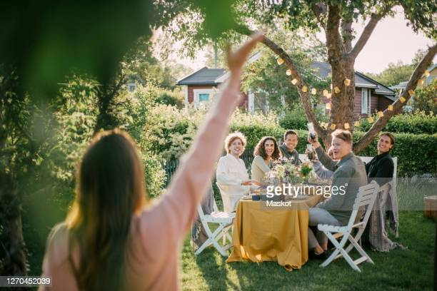 rear view of female waving to friends at garden party - dusk stock pictures, royalty-free photos & images