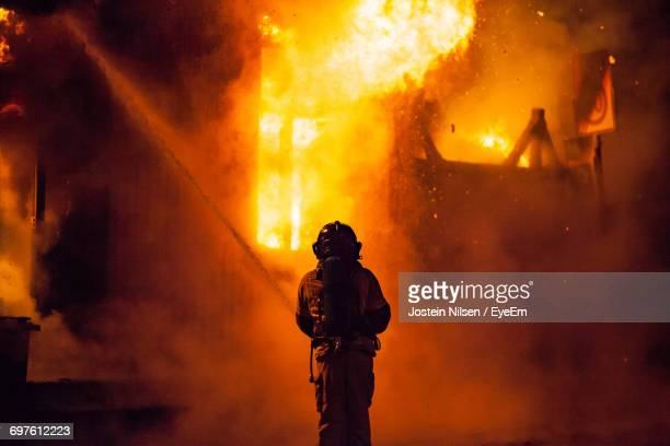 rear view of firefighter at night - firefighter stock pictures, royalty-free photos & images