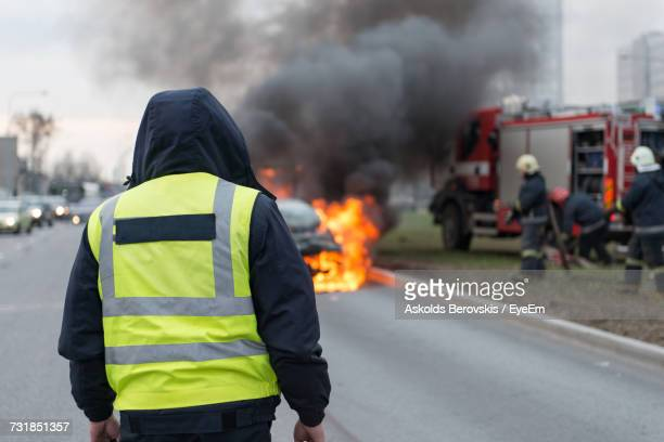 rear view of firefighter on street - reflective clothing stock pictures, royalty-free photos & images