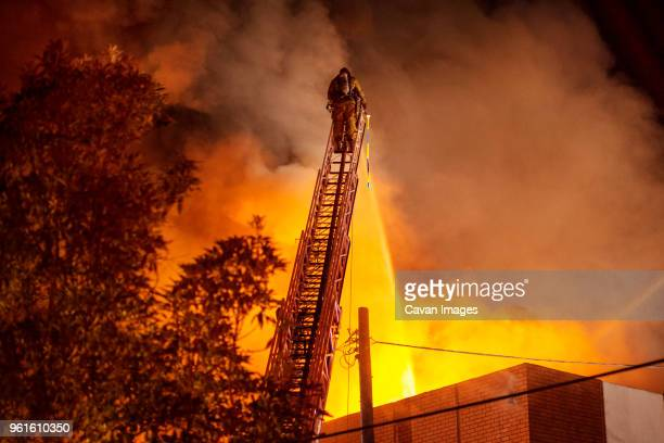 rear view of firefighter spraying water on burning building - fire protection suit - fotografias e filmes do acervo