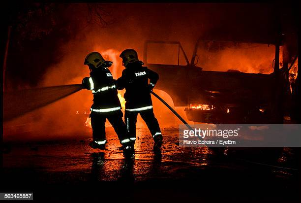 rear view of firefighters in uniform spraying water against smoke at night - goiania imagens e fotografias de stock