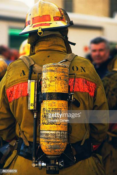 Rear view of fireman wearing oxygen tank