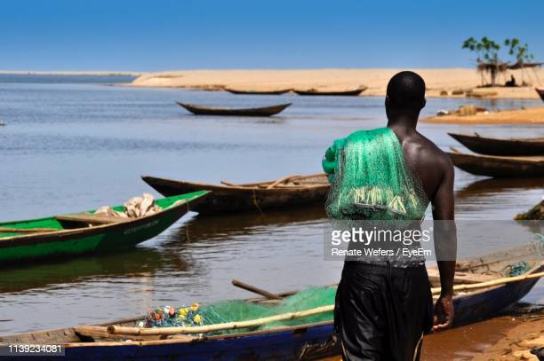 rear view of fisherman standing at shore - ghana africa fotografías e imágenes de stock