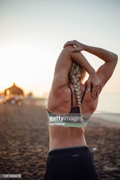 Vista posterior de forma mujer con brazos levantados en la playa