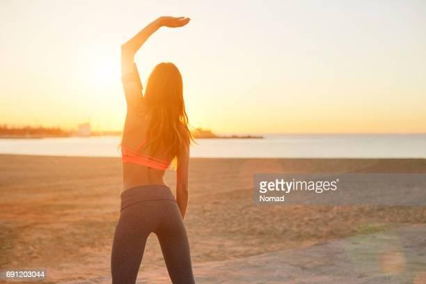 rückansicht des fit frau mit hand am strand - dreiviertelansicht stock-fotos und bilder