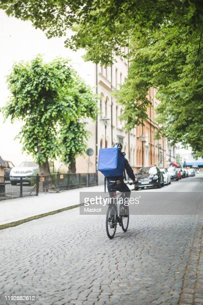 rear view of food delivery man riding bicycle on street in city - montare foto e immagini stock