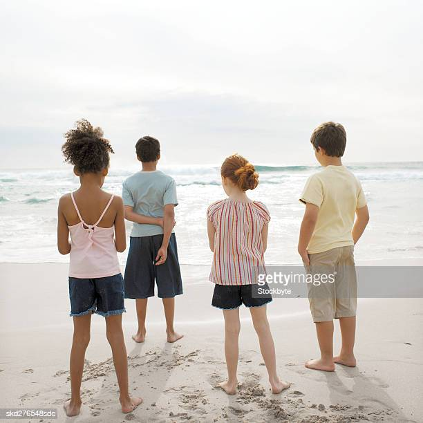 Rear view of four children standing on beach (10-12)