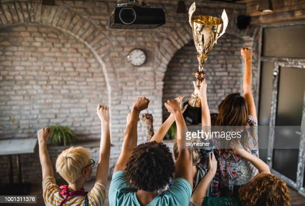 Rear view of freelance team celebrating winning a trophy at casual office.