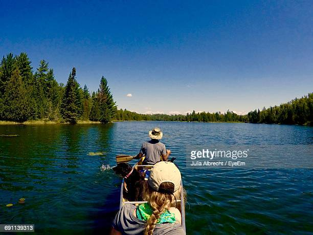 Rear View Of Friends Canoeing With Dog On Lake Against Blue Sky