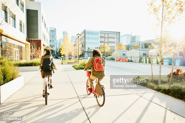 rear view of friends commuting to work on electric bike share bikes - sustainability stock pictures, royalty-free photos & images