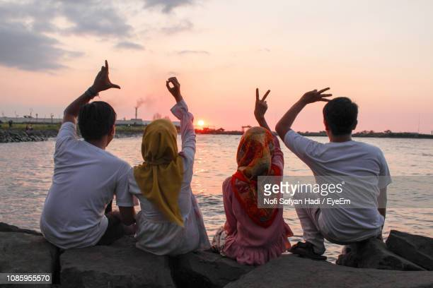 rear view of friends gesturing love text at beach against sky - muslim woman beach stock photos and pictures