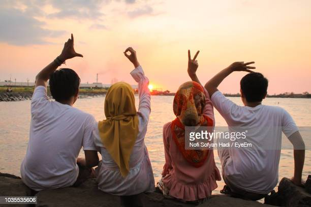 Rear View Of Friends Gesturing While Sitting On Rocks Against Sea During Sunset