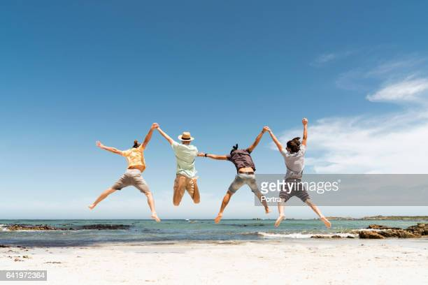 Rear view of friends jumping at beach