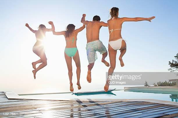 Vista posterior de amigos salto en piscina