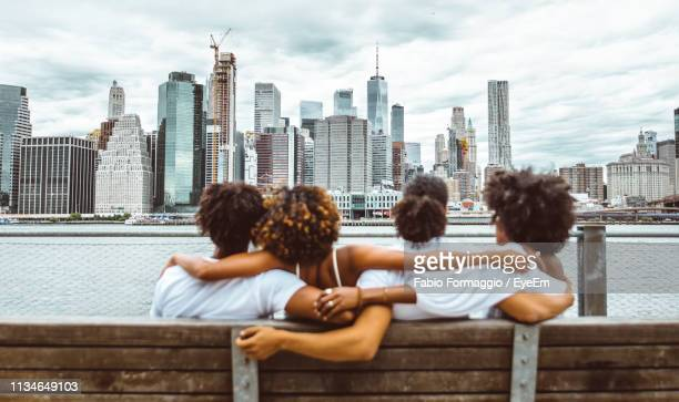 rear view of friends looking at cityscape by river - afro americano - fotografias e filmes do acervo