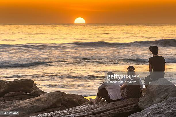 Rear View Of Friends Looking At Sunset While Sitting On Rocks