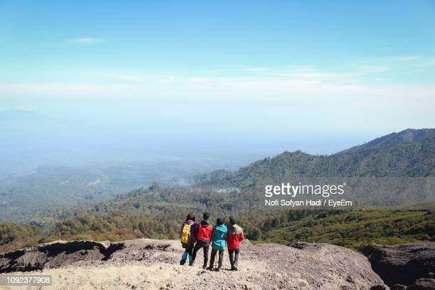 Rear View Of Friends Looking At View While Standing On Mountain Against Sky During Sunny Day