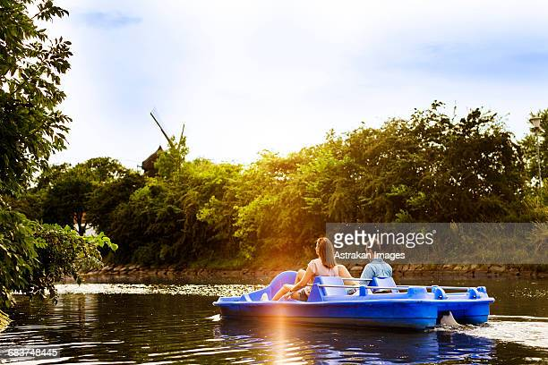 Rear view of friends pedal boating on river against sky