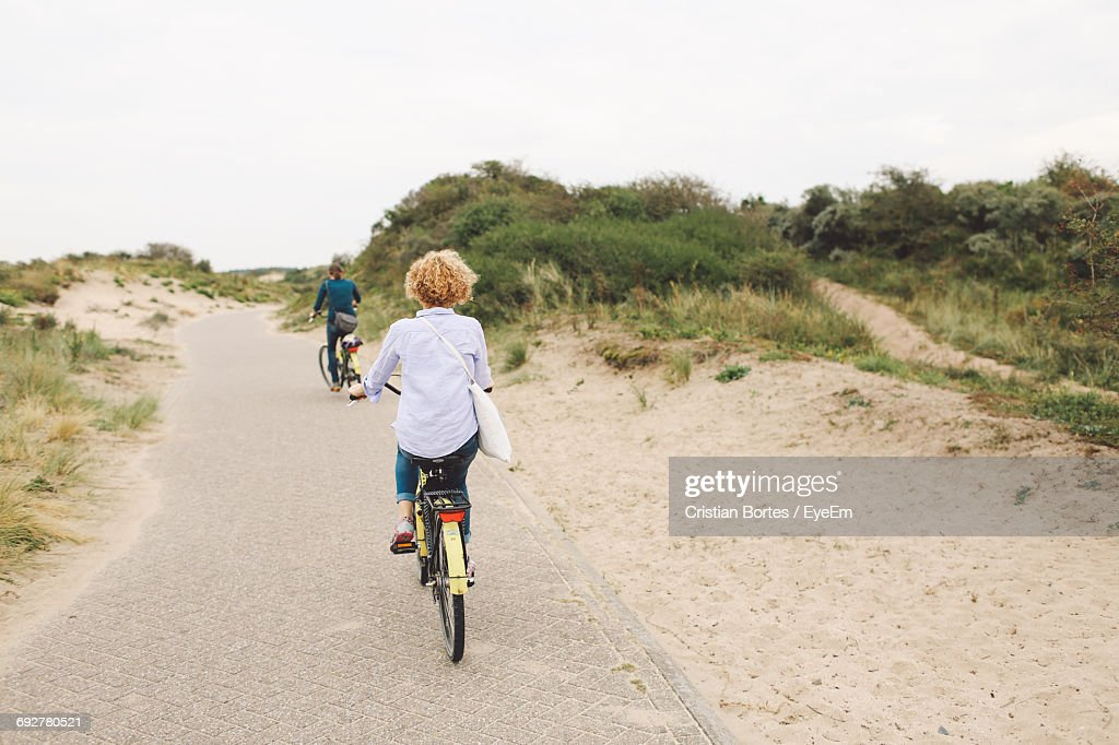 Rear View Of Friends Riding Bicycles On Footpath At Beach : Stock Photo