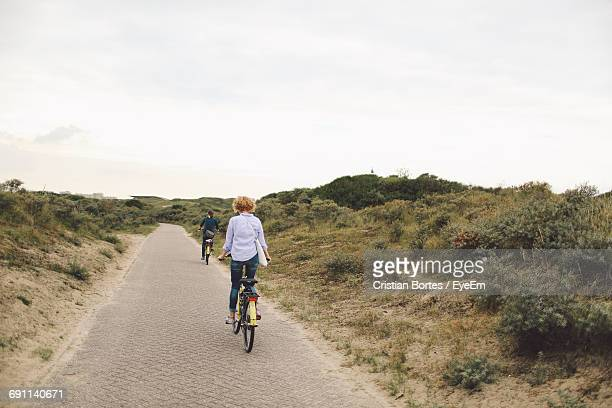 rear view of friends riding bicycles on road against sky - bortes stock-fotos und bilder