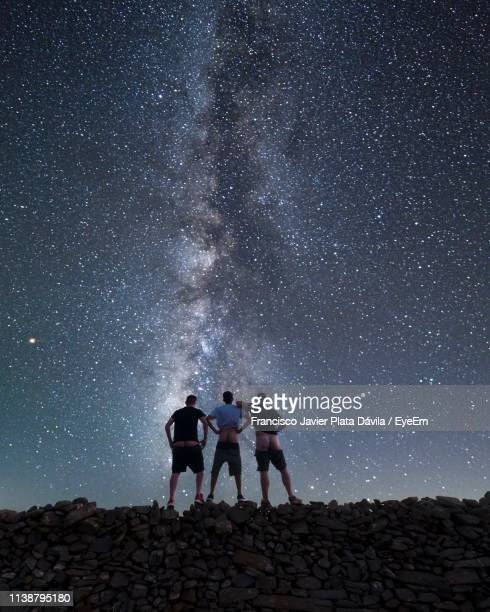 rear view of friends showing buttocks while standing on stone wall against star field - fanny stock pictures, royalty-free photos & images