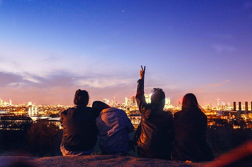 Rear View Of Friends Sitting Against Sky In City At Dusk - gettyimageskorea