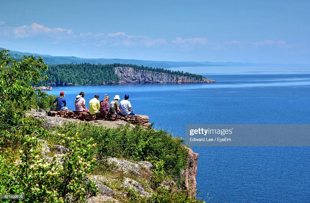 Rear View Of Friends Sitting At Palisade Head Peak While Looking At Lake Superior : Stock Photo