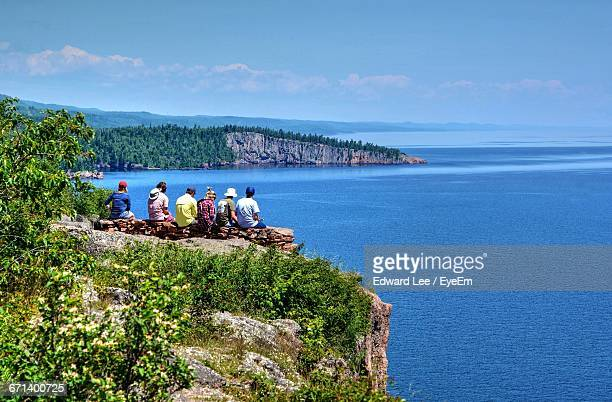 rear view of friends sitting at palisade head peak while looking at lake superior - lake superior stock pictures, royalty-free photos & images