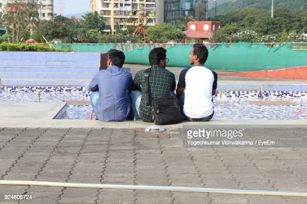 Rear View Of Friends Sitting At Swimming Pool