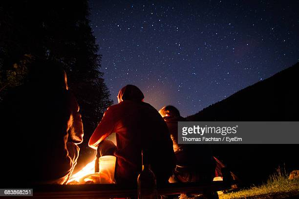rear view of friends sitting by campfire against star field - lagerfeuer stock-fotos und bilder