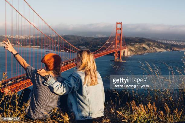 Rear View Of Friends Sitting By Suspension Bridge Against Sky