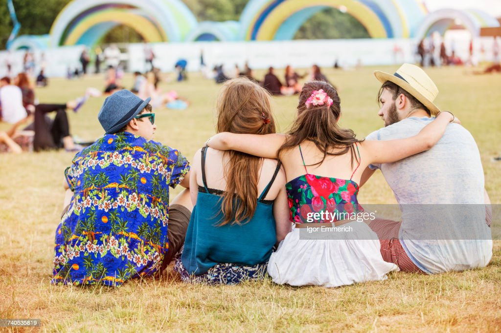 Rear view of friends sitting on grass at festival : Stock Photo