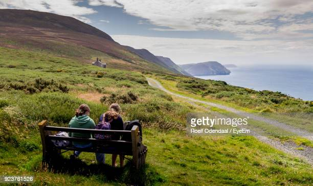 Rear View Of Friends Sitting On Mountain By Sea