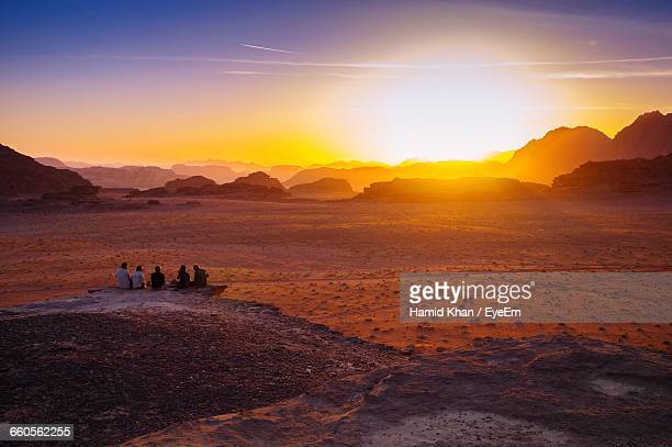rear view of friends sitting on rock at wadi rum during sunset - jordan middle east stock pictures, royalty-free photos & images