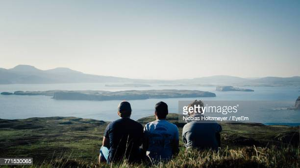Rear View Of Friends Sitting On Shore Against Clear Sky