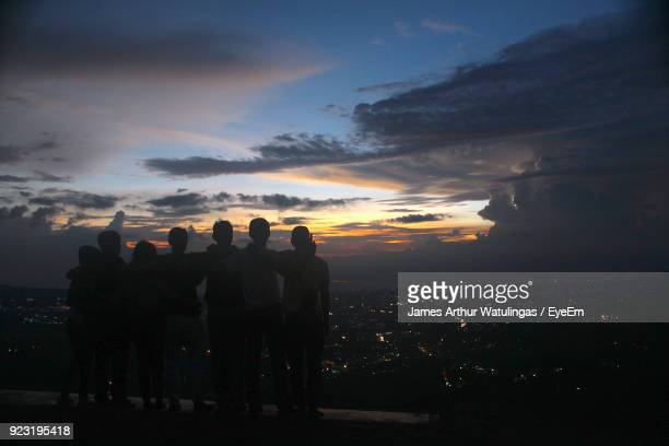 rear view of friends standing against cityscape during sunset - bogor stock pictures, royalty-free photos & images