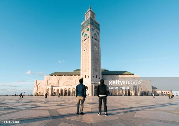 Rear view of friends standing against Mosque Hassan II