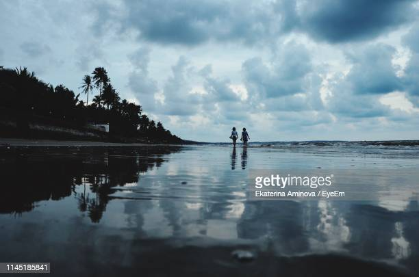 rear view of friends standing at beach against cloudy sky - pretty vietnamese women stock pictures, royalty-free photos & images