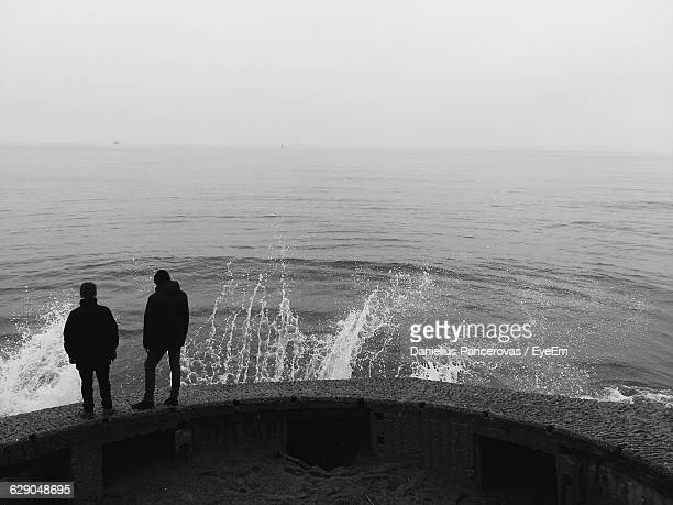 Rear View Of Friends Standing On Retaining Wall Against Sea