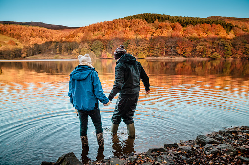 Rear View Of Friends Standing On Water At Ladybower Reservoir - gettyimageskorea