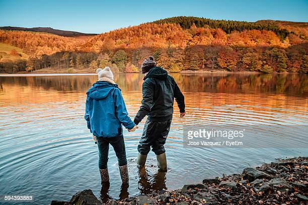 Rear View Of Friends Standing On Water At Ladybower Reservoir