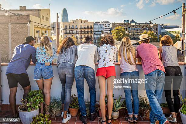 Rear view of friends standing together on terrace